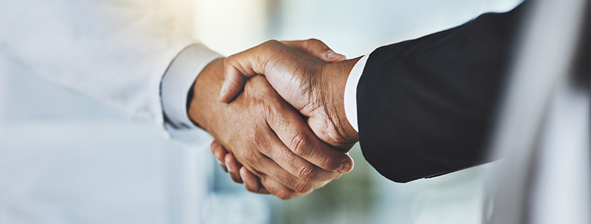 Doctor and business man shaking hands